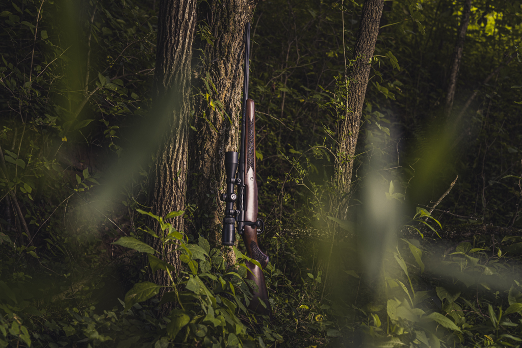 a photo of a hunting rifle leaning against a tree in a forrest