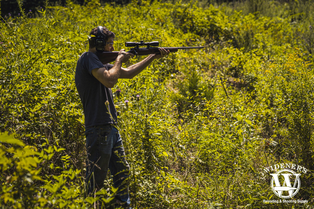 A photo of a man shooting a 30-06 hunting rifle outdoors