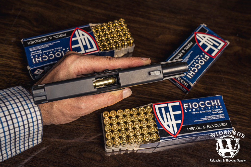 a photo of a man holding a 9mm pistol next to fiocchi ammo