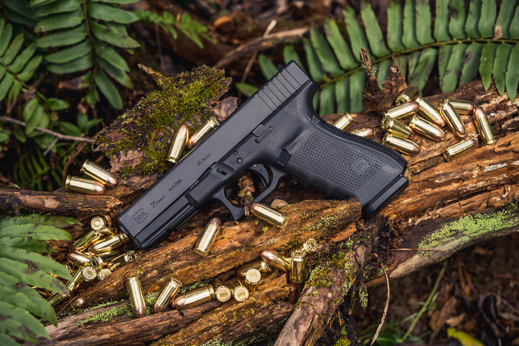 photo of a glock 21 45 acp handgun outdoors with ammo