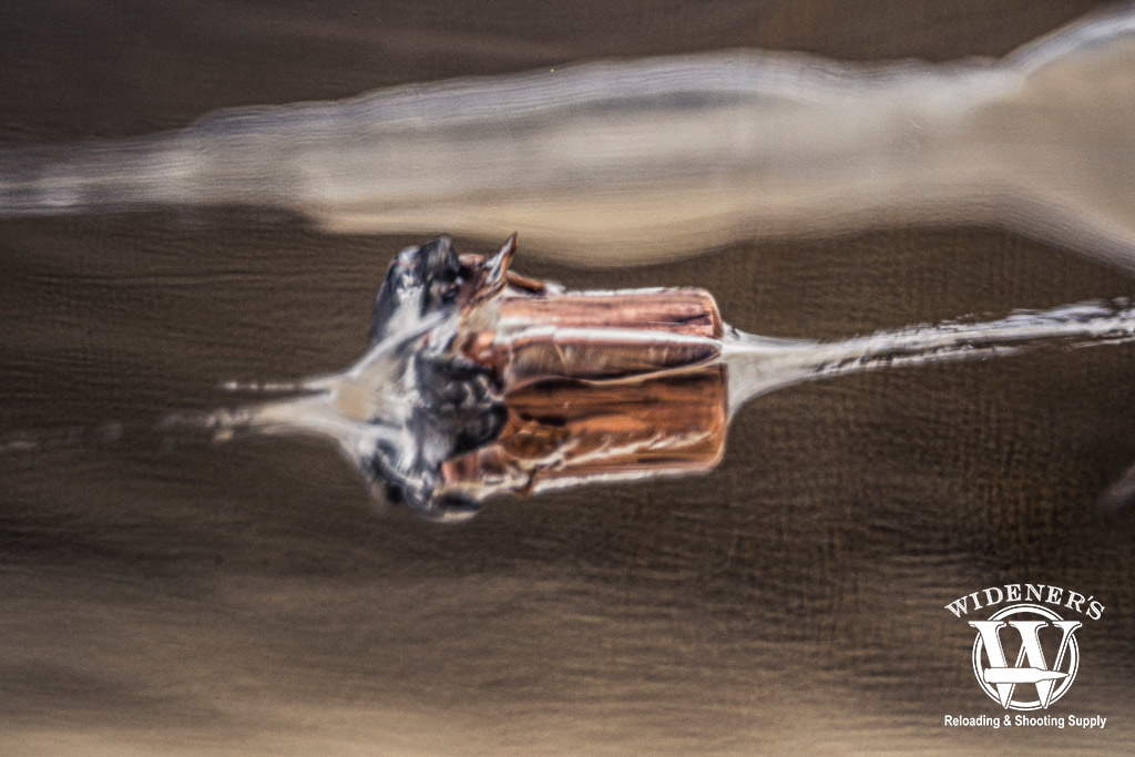 a photo of a jhp bullet suspended in a block of ballistic gel
