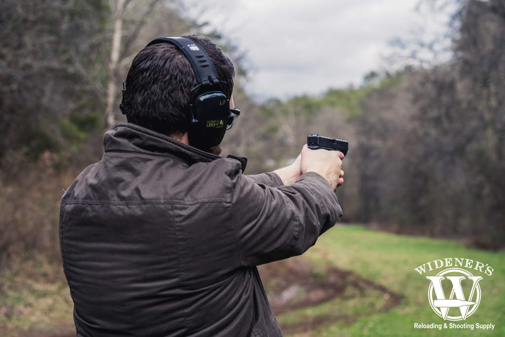 a photo of a man shooting a glock 21 handgun chambered in 45 acp