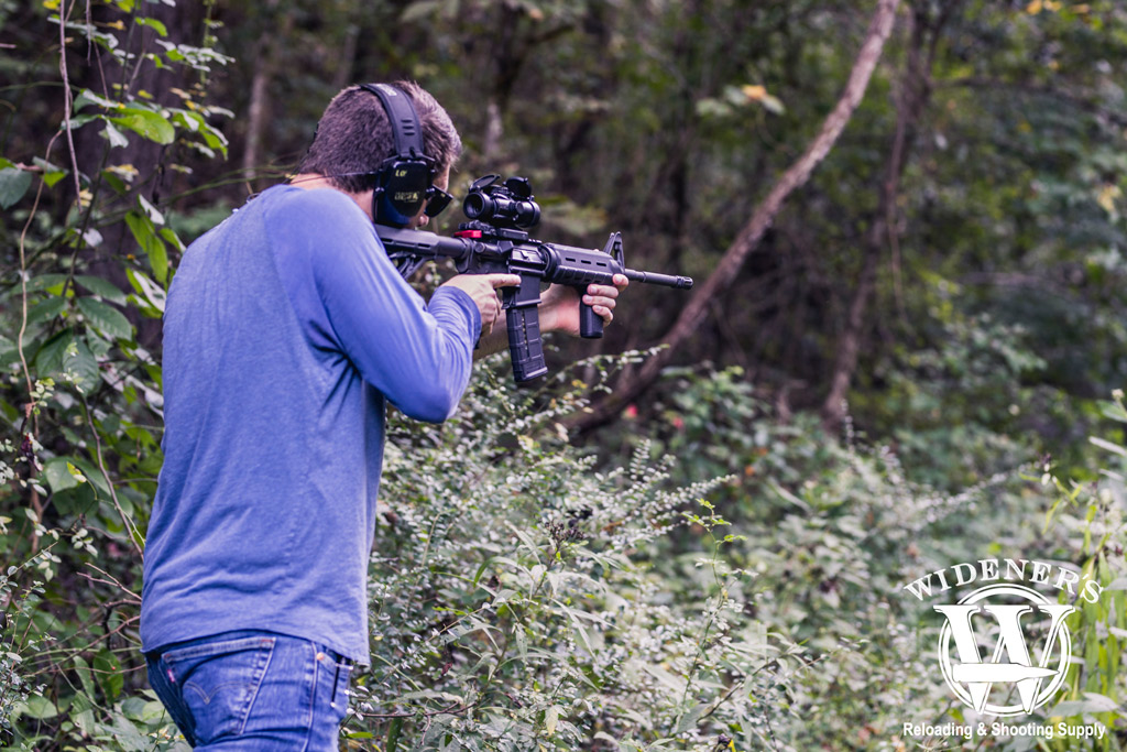photo of a man in the woods shooting an ar15 rifle with 223 ammo illustrating the history of the ar-15