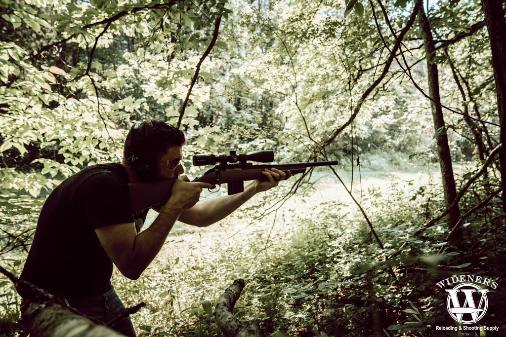 photo of a man in the woods shooting the ruger american rifle chambered in 350 legend