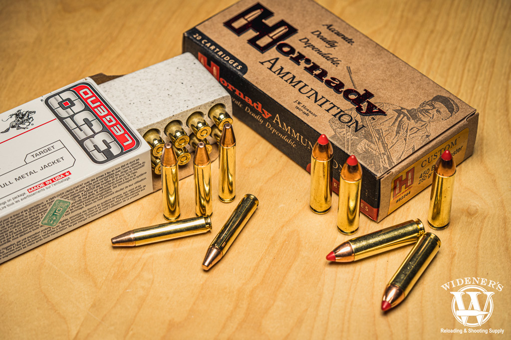 A photo of 350 legend ammo next to 450 bushmaster ammo on a sheet of plywood.