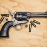 a photo of a colt navy revolver on plywood