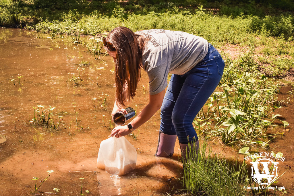 a photo of a woman gathering water for testing in a rubber bladder