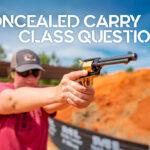 a photo of concealed carry class instructor firing a pistol at an outdoors gun range