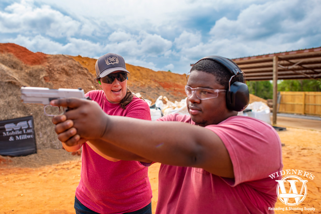 a photo of an african american male shooting at an outdoor pistol range
