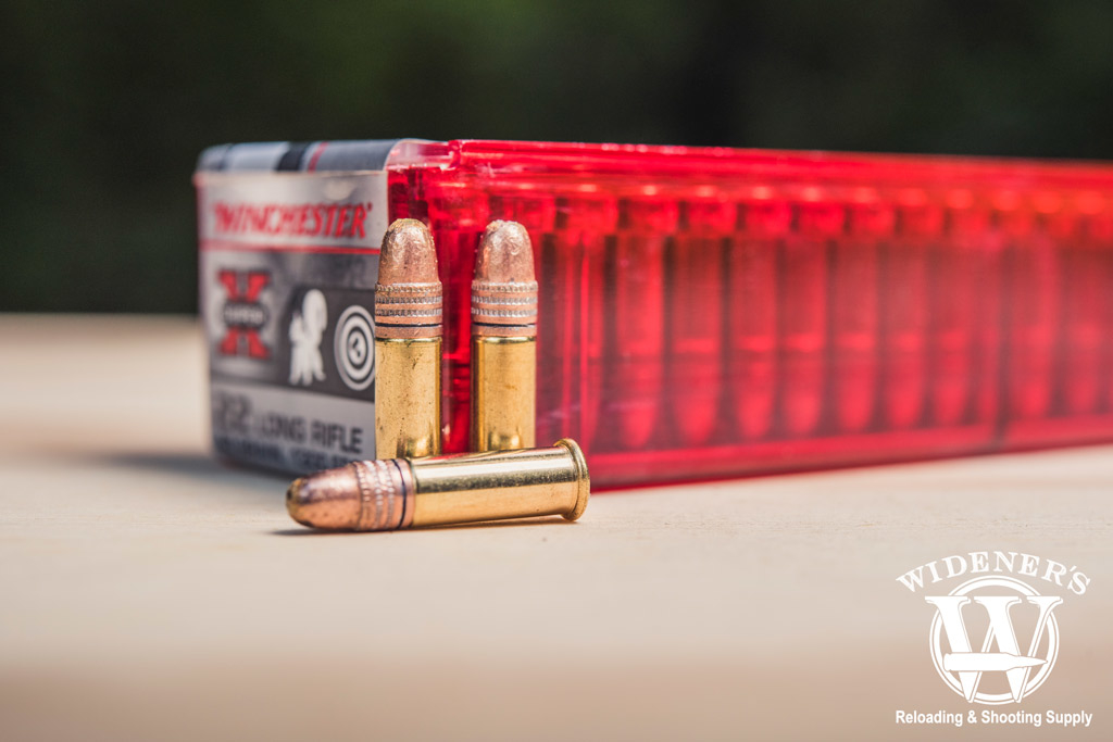 photo of winchester .22 LR ammo sitting outside on a sheet of plywood