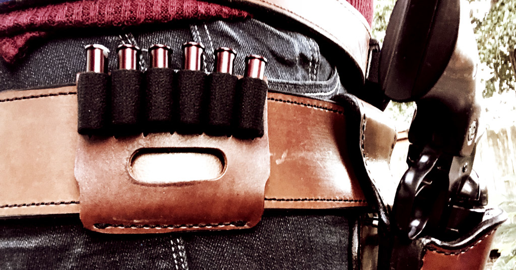 a photo of A leather slide with 5 bullet loops for holding rifle ammo at a Cowboy Action Stage
